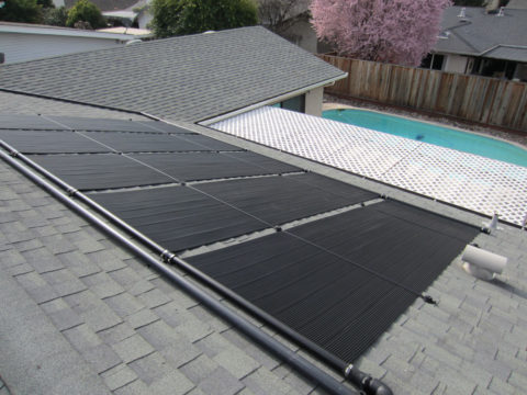 Swimming pool solar heater installed on a shingle roof.